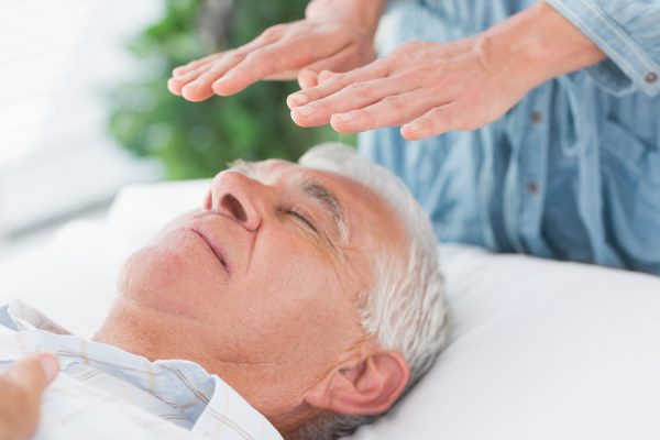 Man receiving Healing Touch therapy from a Mind-Body Energy Medicine specialist.
