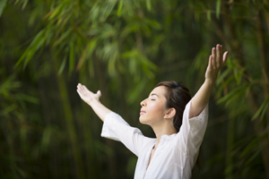 Woman practicing QiGong in a garden as part of a healthy lifestyle and relaxation therapy.