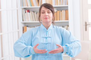 Woman practicing Qigong wearing professional, original Chinese clothes, at home