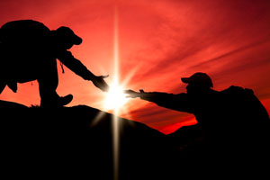 Silhouette of helping hand between a client with cancer and her mid-body energy medicine specialist