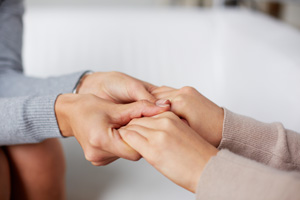 Close-up of spiritual counselor hands holding those of her client